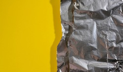 crumpled sheet of gray foil for packaging products with torn edges on a yellow background, flat lay, copy space