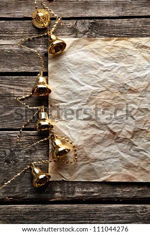 Crumpled sheet of paper with Christmas gold bells on old wood. With space for text.