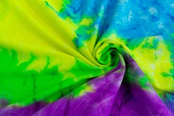 Crumpled tie dye colourful (yellow, gree, blue, purple) fabric texture and background