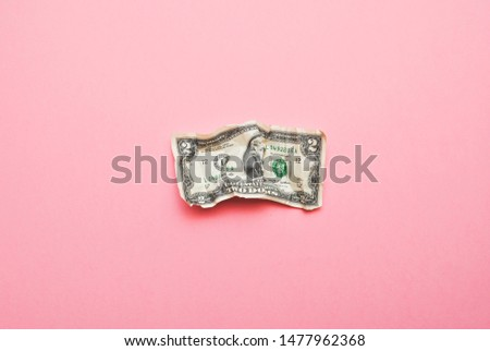 Crumpled two US dollar bill isolated on pink background