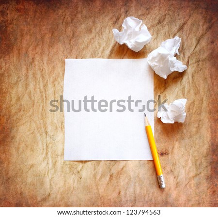 crumpled up papers with a sheet of blank paper and pencil