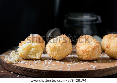 Crunchy coconut cookies Congolais on a wooden board against a dark background