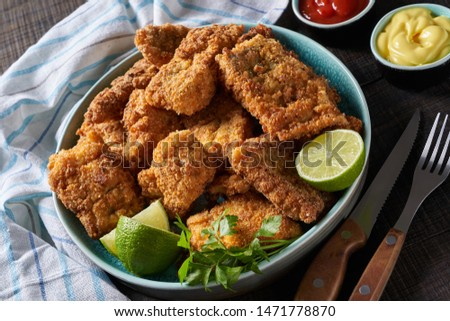 Crunchy cod fillet - healthy full of fatty acid dinner option served with sauces, lime and parsley sprigs on a blue plate with cutlery on a wooden background, close-up, horizontal orientation