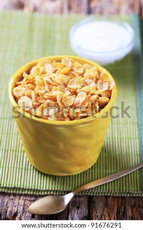 Crunchy corn flakes and bowl of sour cream
