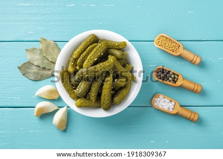 Crunchy pickled cornichons in a white ceramic bowl, garlic, bay leaves, salt, pepper and mustard seeds over blue wooden table. Marinated green gherkins. Delicious baby pickles. Tasty canned vegetables Photo stock ©