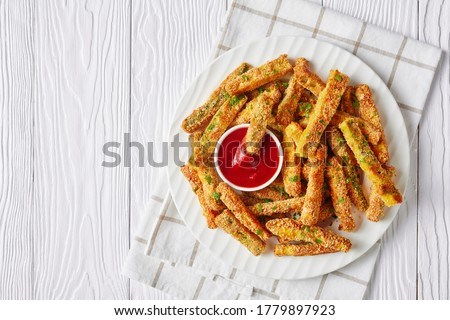crunchy zucchini sticks breaded with panko breadcrumbs, parmesan cheese, spices on a white plate with ketchup on a wooden table, view from above, flat lay, free space