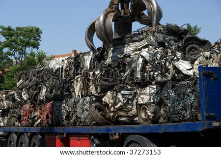 Crushed cars being put on a truck