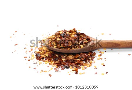 Crushed dry, spicy pepper, chili flakes and seeds in wooden spoon isolated on white background
