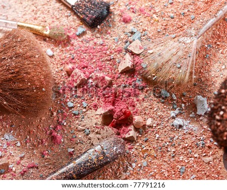 Crushed eyeshadows with professional make-up brush, closeup on wooden art palette