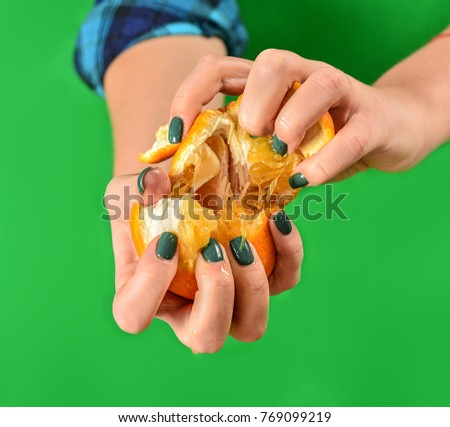 crushed orange in hands on a green background #769099219