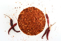 Crushed red cayenne pepper, dried chili flakes in a white bowl, isolated on white background, Top view.