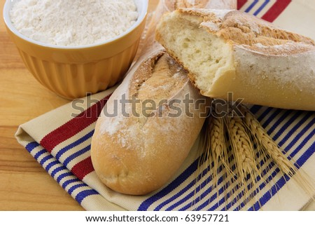 Crusty bread with flour and wheat stalks illustrate tasty food and wheat allergens
