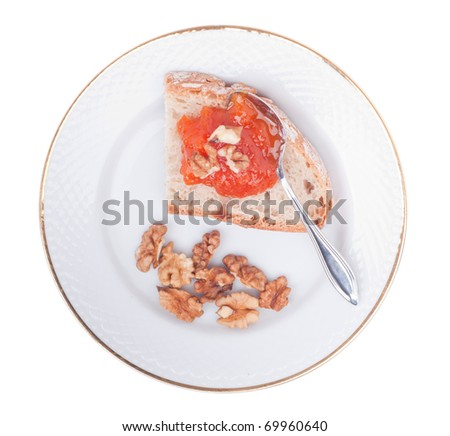 crusty bread with homemade pumpkin jam and walnuts on a plate (isolated on white background)