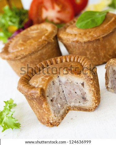 Crusty English pork pie sliced against a background of pies green leaf salad and tomatoes