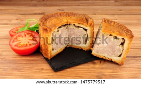 Crusty savoury pork meat pie on a wood background
