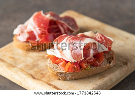 Crusty toast with fresh tomatoes and cured ham. Delicious appetiser Italian prosciutto and Spanish Iberian ham snack Stock photo ©