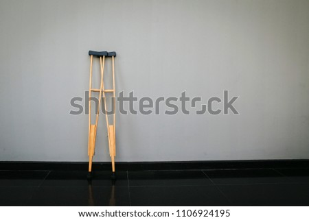 Crutches at wall.Success concept with crutches in the shadow of ladder. Insurance for heath care concept. Pair Of Two Crutches Leaning On White Wall. #1106924195