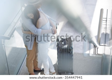 Crying Asian girl hugging her boyfriend in airport as she is leaving