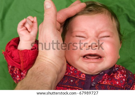 crying baby and fathers protective hand