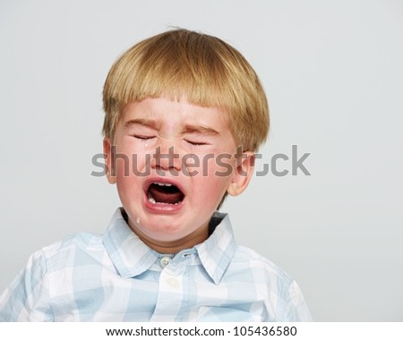 Crying baby boy in checkered shirt
