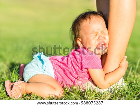 Crying baby girl holding onto mothers leg outdoors.