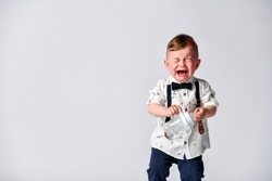 Crying baby. Portrait of a kid in full growth in the studio on a white background. Dressed in a suit of a gentleman - white shirt and pants with straps. Baby Emotions