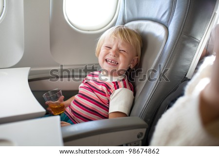 crying child with juice in airplane