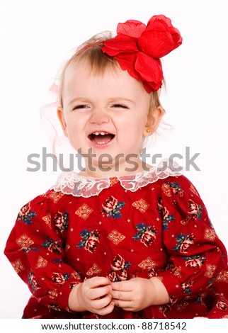 crying child with short hair and red flower hair pin