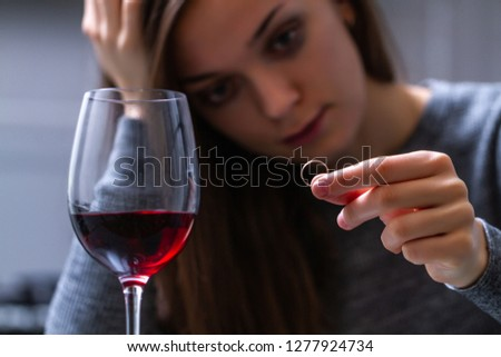 Crying, divorced woman holding a wedding ring and drinking alone a red wine because of adultery, betrayal and failed marriage. Divorce concept. Relationship and love end.  #1277924734