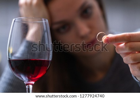 Crying, divorced woman holding a wedding ring and drinking alone a red wine because of adultery, betrayal and failed marriage. Divorce concept. Relationship and love end.  #1277924740