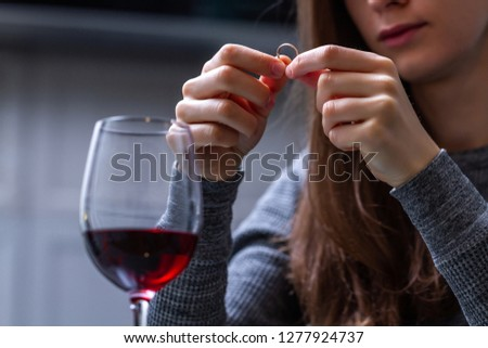 Crying, divorced woman holding a wedding ring and drinking alone red wine because of adultery, betrayal and failed marriage. Divorce concept.  #1277924737