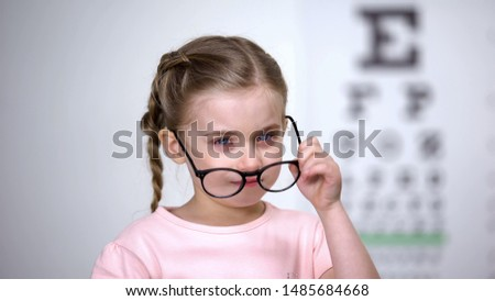 Crying girl taking off glasses, worrying about bullying from peers, insecurities