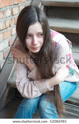 Crying girl with tears sitting on wooden stairs near red brick wall