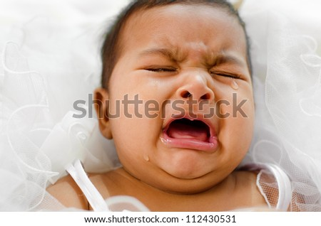 Stock Photo Crying Indian baby girl lying on bed