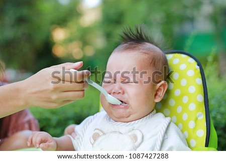 Crying Infant baby boy with first times feeding food.