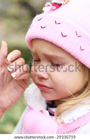 Crying little girl and hand wiping tears.