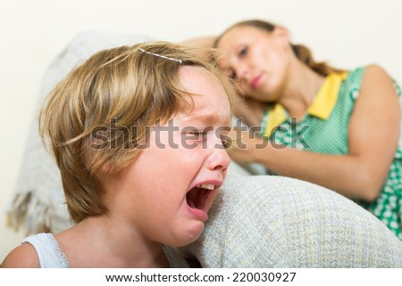 Crying little girl and upset mother sitting on couch at home