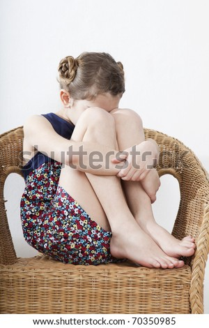 crying  little girl nine years old sitting on chair