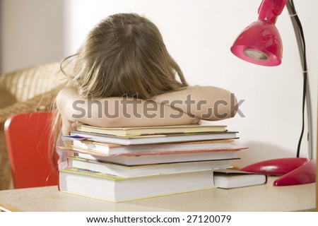 Crying  little girl studying at the desk