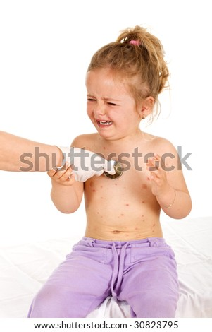Crying little girl with small pox consulted by a physician - isolated - stock photo