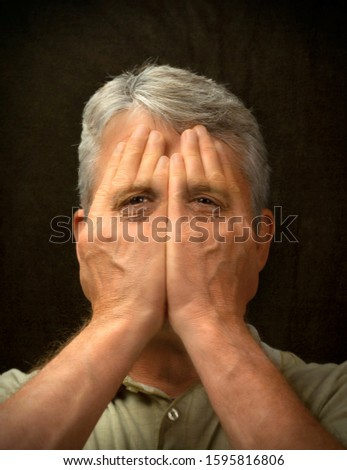 Crying man trying to hide face with his hands to not show his feelings but tear filled eyes are showing through exposing sadness, depression, stress, guilt and fear.