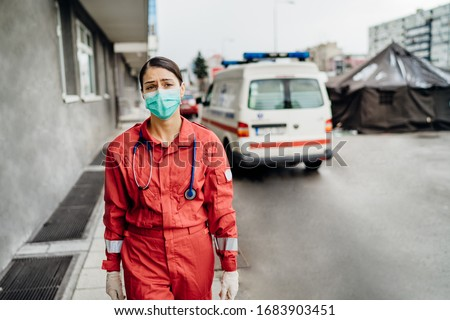 Crying paramedic in front of isolation hospital facility.Mental melt down of medical professional.Emergency room doctor in fear and stress,pressure of fight against corona virus.Covid-19 deaths impact