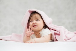 Crying six months old baby girl lying on blanket at home