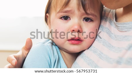 crying toddler girl being...