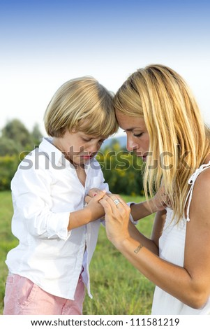Crying young boy showing finger injury to his concerned mother, outdoors in the park