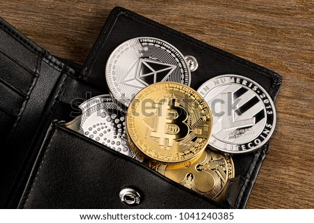 crypto currency coin in leather wallet on wide wood wooden background bitcoin ethereum litecoin iota ripple - Shutterstock ID 1041240385