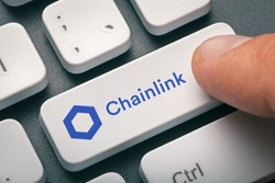 Cryptocurrency trading concept: Male hand pressing computer key with Chainlink   Link logo. Cryptocurrency mining, trading, market concept.