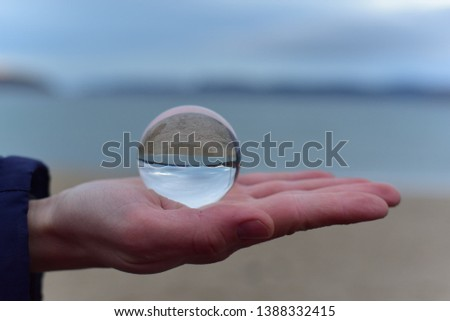 Crystal Ball is on the hand of a guy that reflects the up side down picture. Amazing picture with a tiny ocean.