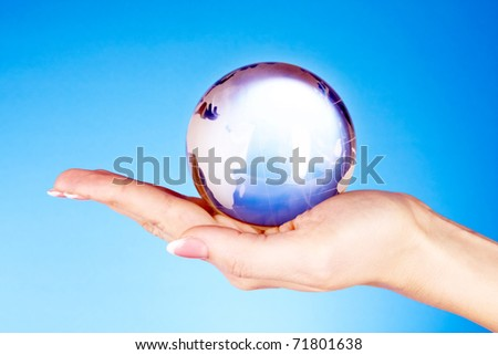 Crystal ball on hand. blue background