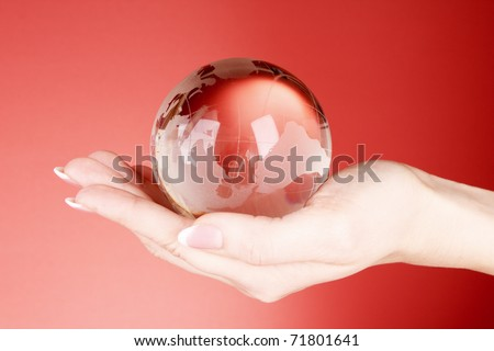 Crystal ball on hand. Red background